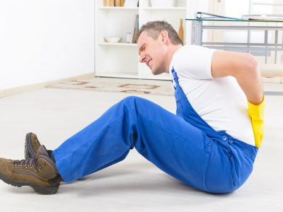 Man worker with back injury, concept of accident at work